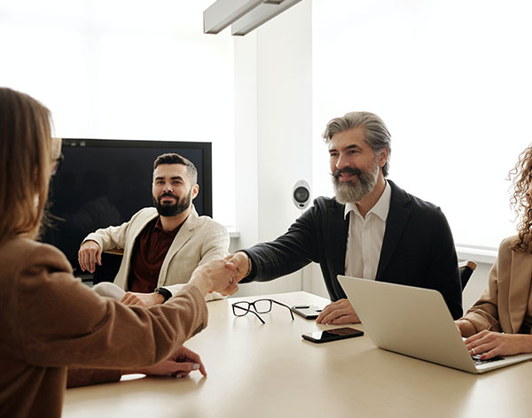 four people at a conference table, two shaking hands