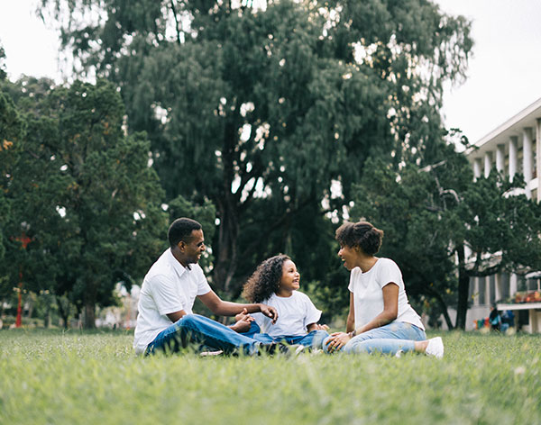 mother, father, and daughter wearing white sitting on the grass